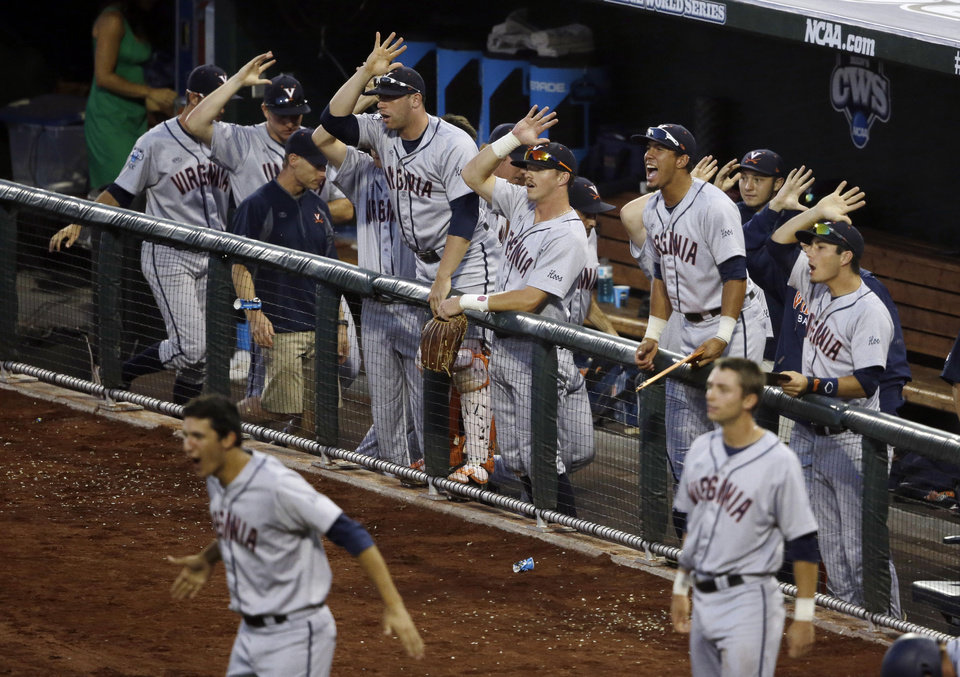 Photo - Players in the Virginia dugout celebrate after Virginia's Brandon Downes hit an RBI triple in the sixth inning of Game 2 of the best-of-three NCAA baseball College World Series finals against Vanderbilt in Omaha, Neb., Tuesday, June 24, 2014. (AP Photo/Nati Harnik)