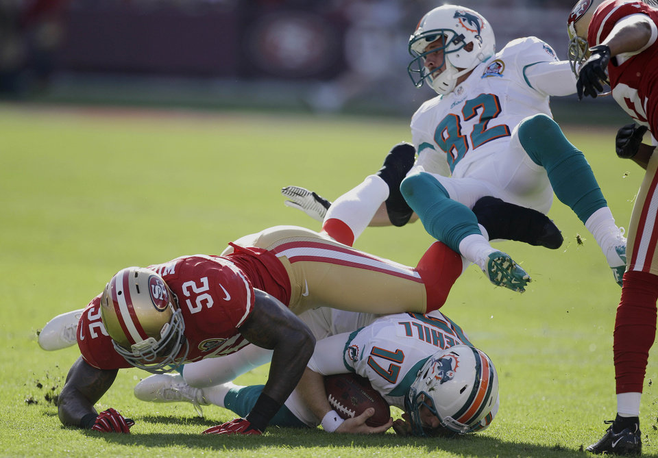 Miami Dolphins quarterback Ryan Tannehill (17) is stopped for a two-yard gain by San Francisco 49ers inside linebacker Patrick Willis (52) during the first quarter of an NFL football game in San Francisco, Sunday, Dec. 9, 2012. At right is Miami Dolphins wide receiver Brian Hartline (82). (AP Photo/Ben Margot)