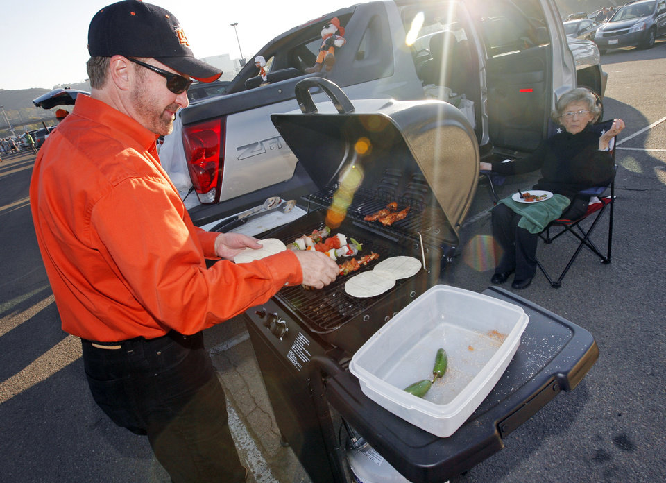 Photo - OSU fan Kent Goodman, of San Diego, grills in the parking lot with his mother, Mayme Jo Guest, of Oklahoma City, before the Holiday Bowl college football game between Oklahoma State and Oregon at Qualcomm Stadium in San Diego, Tuesday, Dec. 30, 2008. Goodman is an OSU graduate and originally from Oklahoma City. PHOTO BY NATE BILLINGS, THE OKLAHOMAN