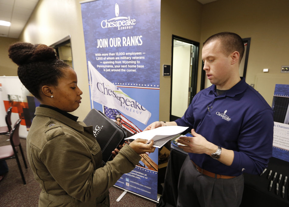 Latasha Brooks, left, gives her resume to Chesapeake Energy Recruiter Jason Allbaugh during a Job Fair at Rose State College in Midwest City, Friday February 22, 2013. Photo By Steve Gooch, The Oklahoman