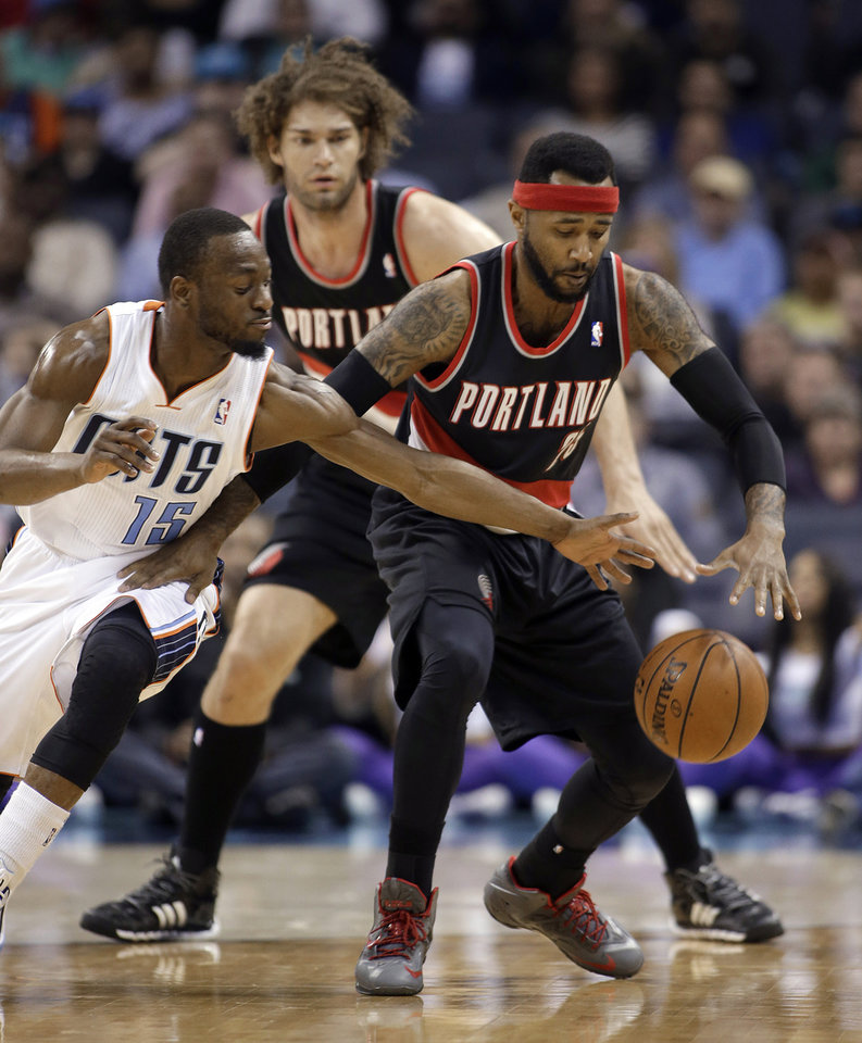 Photo - Charlotte Bobcats' Kemba Walker, left stretches to make a steal from Portland Trail Blazers' Mo Williams, right as Portland Trail Blazers' Robin Lopez watches from behind during the first half of an NBA basketball game in Charlotte, N.C., Saturday, March 22, 2014. (AP Photo/Bob Leverone)