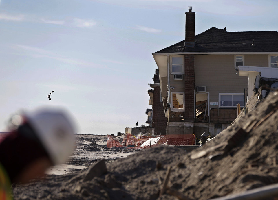 Photo - A construction worker walks on the beach as work continues in the Rockaways cleaning up debris from destroyed homes in the wake of Superstorm Sandy, Thursday, Jan. 10, 2013, in New York.  The November storm damaged or destroyed 305,000 housing units in New York.  (AP Photo/Kathy Willens)