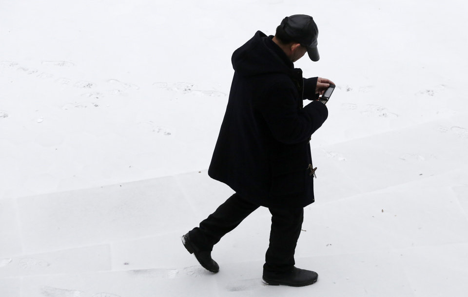 Photo - A man checks his mobile phone as he walks through snow-covered Columbus Park, Monday, March 3, 2014 in New York. Winter kept its icy hold on much of the country Monday, with snow falling and temperatures starting to plummet from the Mid-Atlantic states up to the East Coast. (AP Photo/Mark Lennihan)