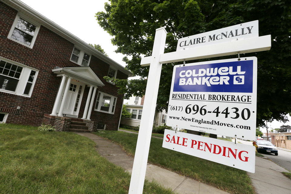In this July 10, 2014 photo, a sale pending sign is posted in front of a home for sale in Quincy, Mass. The National Association of Realtors on Monday, July 28, 2014 said its seasonally adjusted pending home sales index slipped 1.1 percent to 102.7 in June. The index remains 7.3 percent below its level a year ago. (AP Photo/Michael Dwyer)