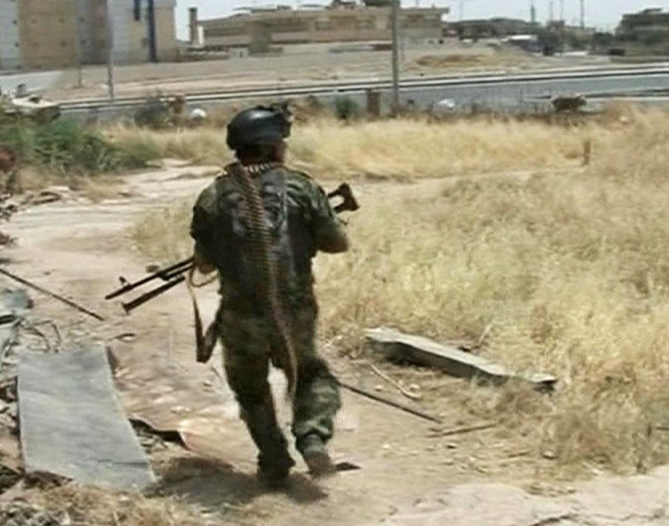 Photo - In this Monday, June 9, 2014 image taken from video obtained from the Iraqi Military, which has been authenticated based on its contents and other AP reporting, an Iraqi armed solider runs for cover during clashes with militants in the northern city of Mosul, Iraq. Insurgents on Tuesday pressed their efforts to seize effective control of Iraq's second-largest city of Mosul on Tuesday after Iraqi security forces abandoned their posts and militants overran the provincial government headquarters and other key buildings, dealing a serious blow to Baghdad's attempts to tame a widening insurgency in the country. (AP Photo/Iraqi Military via AP video)