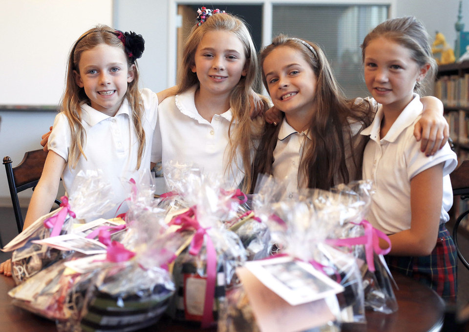 Photo - Third-graders Ally Petree, Hallie Harned, Kirby Johnson and Hannah Potter display gift bags for victims of recent fires. Photo by Sarah Phipps, The Oklahoman