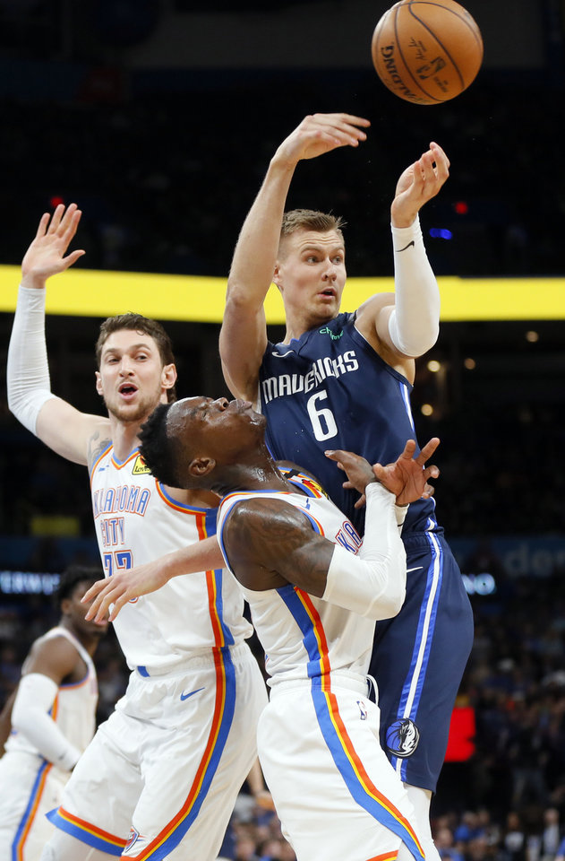 Photo - Dallas' Kristaps Porzingis (6) collides with Oklahoma City's Dennis Schroder (17) as he passes near Oklahoma City's Mike Muscala (33) in the fourth quarter during an NBA basketball game between the Oklahoma City Thunder and Dallas Mavericks at Chesapeake Energy Arena in Oklahoma City, Monday, Jan. 27, 2020. Dallas won 107-97. [Nate Billings/The Oklahoman]