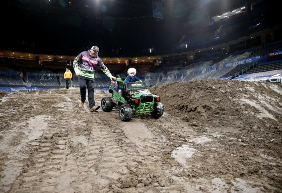 Photo -  Ryker Ammons, 4, drives his minature Grave Digger truck on Friday as Brandon Vinson helps guide him inside Chesapeake Energy Arena.