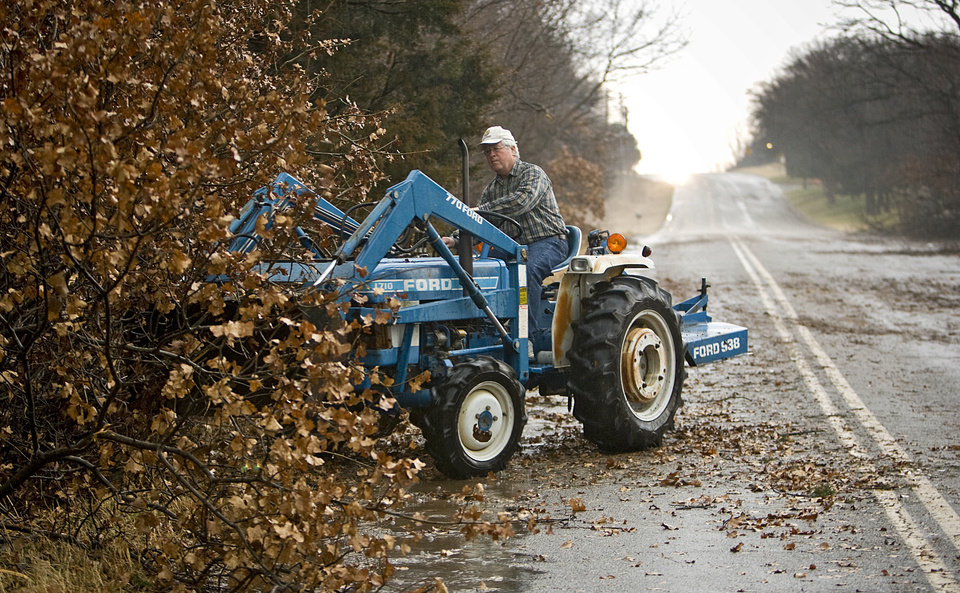 Photo - Clyde Conger uses his tractor to clear storm debris from Waterloo Road after storms hit the area on Tuesday, Feb. 10, 2009, in Edmond, Okla.  PHOTO BY CHRIS LANDSBERGER, THE OKLAHOMAN