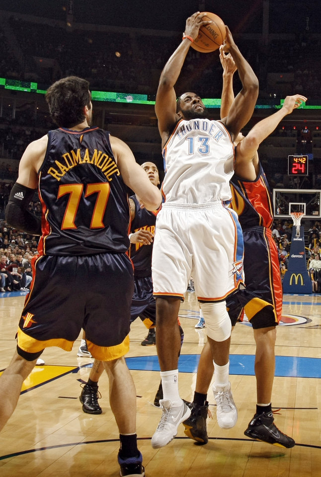 Photo - Oklahoma City's James Harden (13) battles under the basket with Golden State's Stephen Curry (30) and Vladimir Radmanovic (77) during the first half of the NBA basketball game between the Oklahoma City Thunder and the Golden State Warriors at the Ford Center on Monday, Dec. 7, 2009, in Oklahoma City, Okla.   Photo by Chris Landsberger, The Oklahoman ORG XMIT: KOD