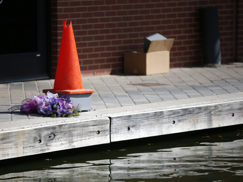 Photo -  Flowers lay where two men were shocked Sunday night after one fell into the Bricktown canal. [Photo by Sarah Phipps, The Oklahoman]