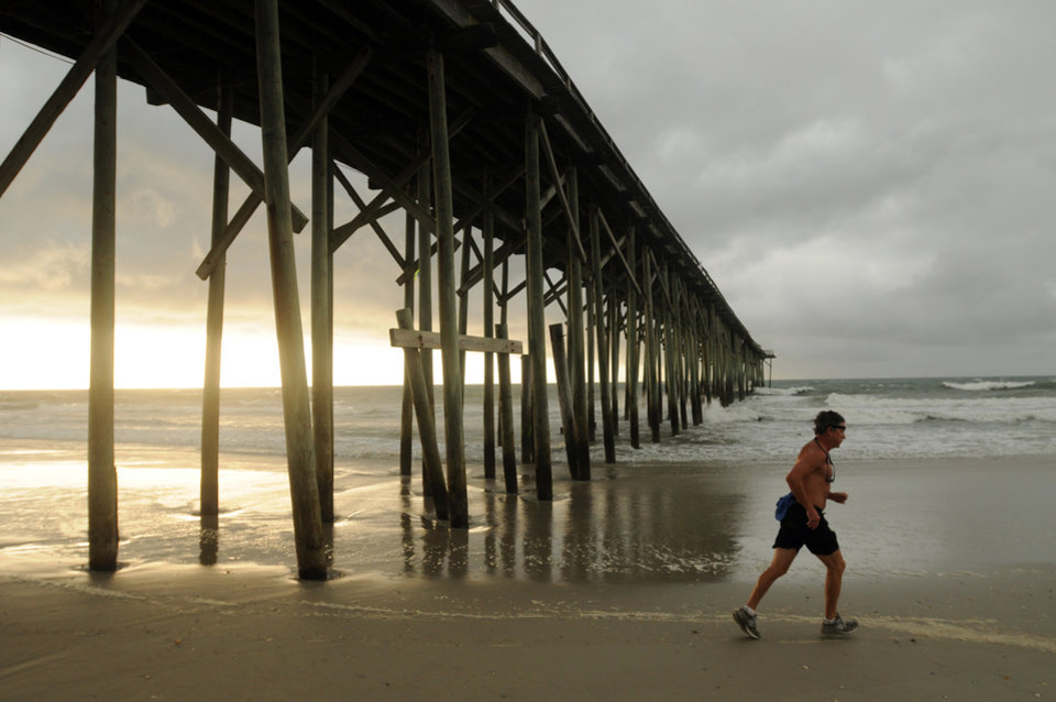 Photo - Clouds and rain move in as a man jogs along the shore of the north end of Carolina Beach, N.C., Thursday, July 3, 2014. Residents along the coast of North Carolina are bracing for the arrival of the Hurricane Arthur, which threatens to give the state a glancing blow on Independence Day. (AP Photo/Wilmington Star-News, Mike Spencer)