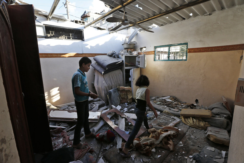 Photo - Palestinian siblings Samih, left and Shaima Hossen inspect the damages of their home after it was heavily damaged from falling debris from the next door apartment building of el-Yazje family, destroyed by an overnight Israeli missile strike in Gaza City, Thursday, July 17, 2014. The Israeli military says it has struck 37 targets in Gaza ahead of a five-hour humanitarian cease-fire meant to allow civilians to stock up after 10 days of fighting. The Gaza Interior Ministry says four people were killed and that a 75-year-old woman died of wounds from the day before. The Israeli army says Hamas fired 11 rockets at Israel early Thursday. Palestinian health officials say that in total, 227 Palestinians have been killed. On the Israeli side, one man was killed since July 8.(AP Photo/Lefteris Pitarakis)