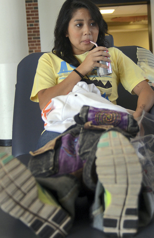 Photo - Tiffany Yu, a sophomore at Oklahoma State University, sips on her drink while being prepped to give blood for the Bedlam Blood Battle. Photo by Adam Kemp, The Oklahoman