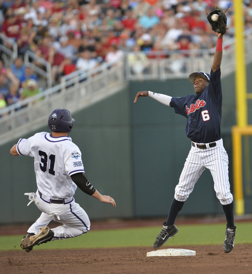 Photo - TCU's Jerrick Suiter (31) is out at second base by Mississippi shortstop Errol Robinson (6), in the fourth inning of an NCAA baseball College World Series elimination game in Omaha, Neb., Thursday, June 19, 2014. TCU's Garrett Crain reached first base on a fielder's choice. (AP Photo/Ted Kirk)