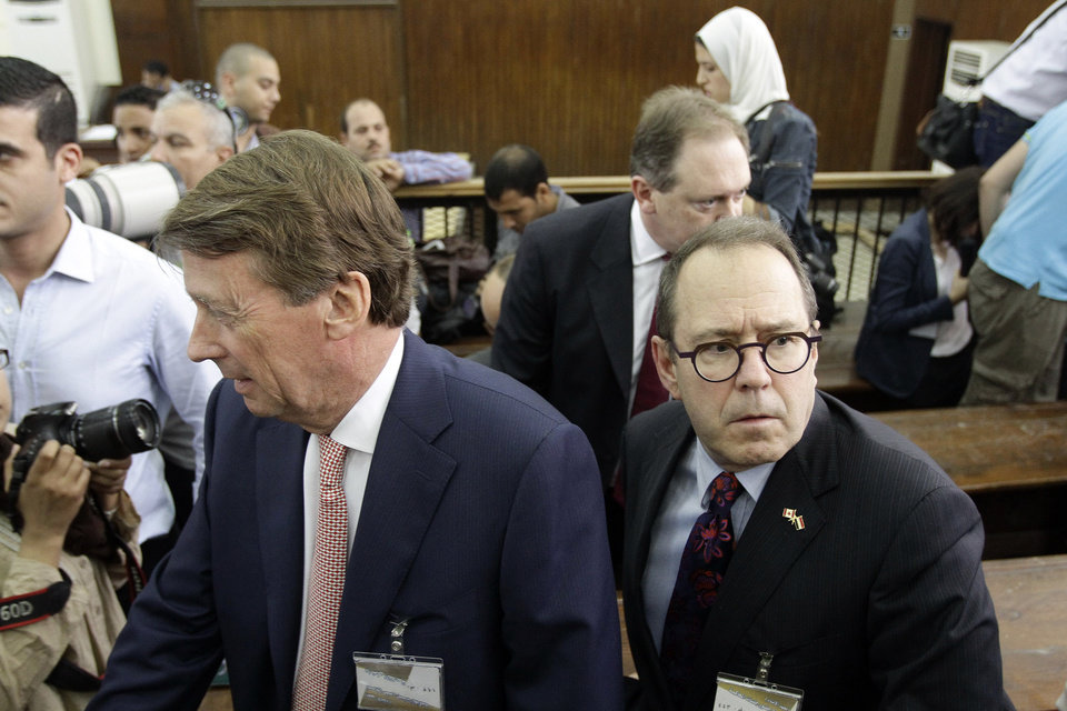 Photo - The Canadian ambassador to Egypt, David Drake, center right, and British ambassador James Watt, center left, attend the sentencing hearing for Al-Jazeera journalists, in a courtroom in Cairo, Egypt, Monday, June 23, 2014. An Egyptian court on Monday convicted three journalists from Al-Jazeera English and sentenced them to seven years in prison each on terrorism-related charges, bringing widespread criticism that the verdict was a blow to freedom of expression. The three, Australian Peter Greste, Canadian-Egyptian Mohamed Fahmy and Egyptian Baher Mohammed, have been detained since December charged with supporting the Muslim Brotherhood, which has been declared a terrorist organization, and of fabricating footage to undermine Egypt's national security and make it appear the country was facing civil war.  (AP Photo/Ahmed Abd El Latif, El Shorouk Newspaper) EGYPT OUT
