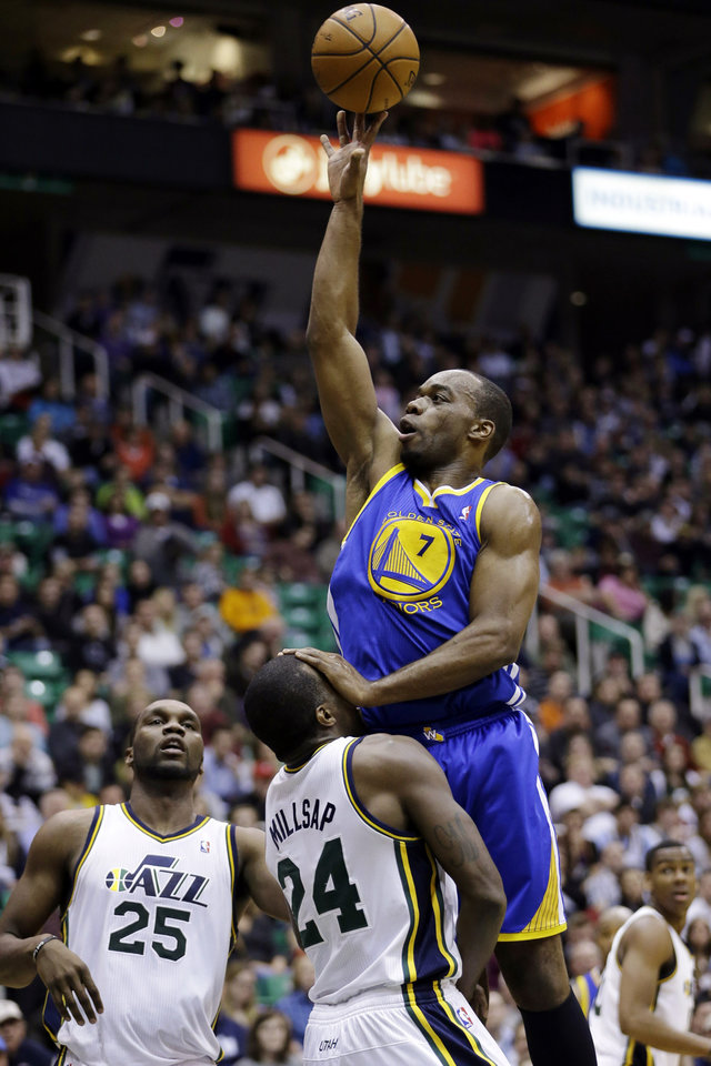 Photo - Golden State Warriors forward Carl Landry (7) fouls Utah Jazz power forward Paul Millsap as he goes to the basket in the second quarter of an NBA basketball game, Wednesday, Dec. 26, 2012, in Salt Lake City. (AP Photo/Rick Bowmer)