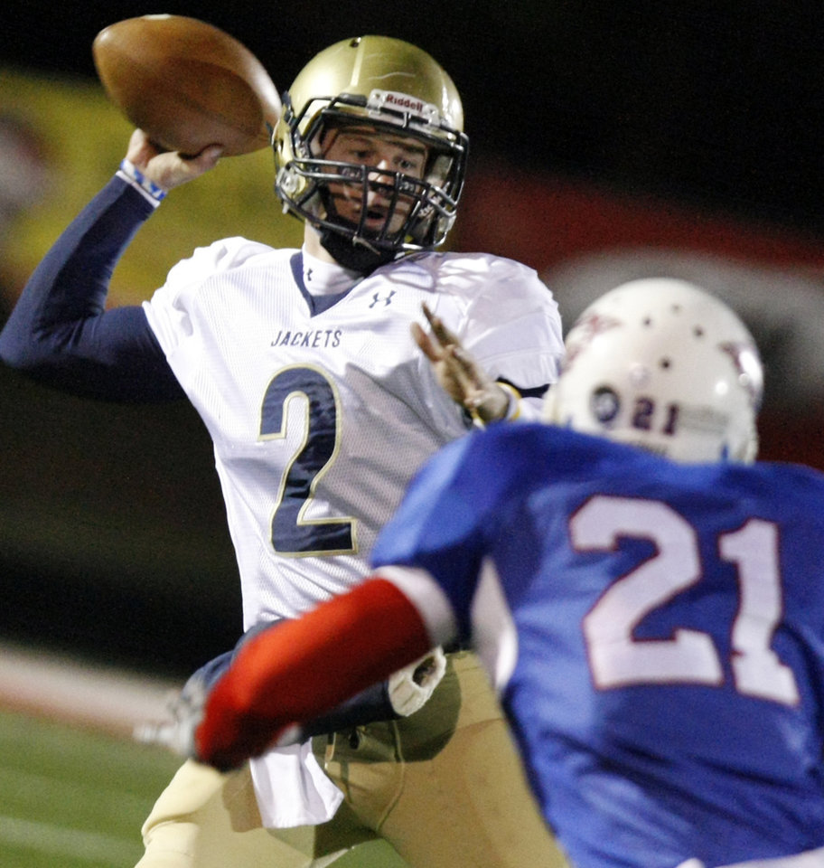 Photo - Kingfisher quarterback Derek Patterson (2) looks to throw the ball past Millwood's Deon Sanders (21) during the Class 2A State semifinal football game between Millwood High School and Kingfisher High School on Saturday, Dec. 5, 2009, in Yukon, Okla. 