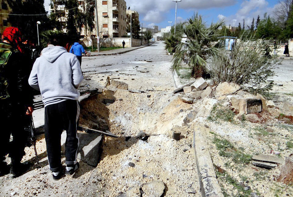Photo - This citizen journalism image and provided by Aleppo Media Center AMC, which has been authenticated based on its contents and other AP reporting, shows Free Syrian Army fighters next to a hole allegedly made during an airstrike by government forces, in Aleppo, Syria, Tuesday, Feb. 12, 2013. Rebels captured a military air base in northern Syria on Tuesday, handing opposition fighters their second strategic victory in their nearly two-year battle against President Bashar Assad in as many days, activists said. (AP Photo/Aleppo Media Center AMC)