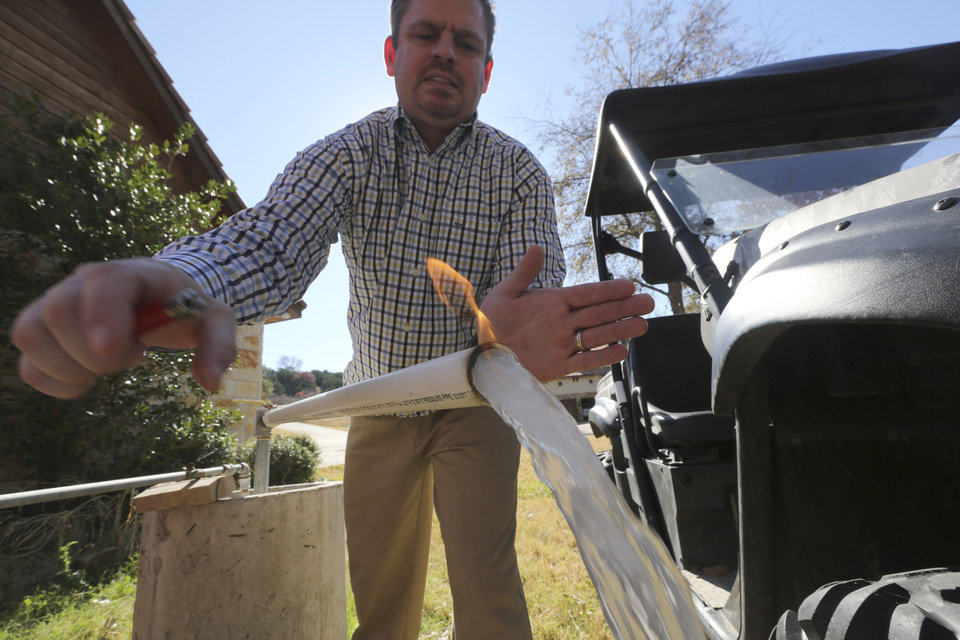 In this Nov. 26, 2012 photo, Steve Lipsky demonstrates how his well water ignites when he puts a flame to the flowing well spigot outside his family's home in rural Parker County near Weatherford, Texas. The U.S. Environmental Protection Agency had evidence a gas company's drilling operation contaminated Lipsky's drinking water with explosive methane, and possibly cancer-causing chemicals, but withdrew its enforcement action, leaving the family with no useable water supply, according to a report obtained by The Associated Press. The EPA's decision to roll back its initial claim that hydraulic fracturing, or �fracking,� operations had contaminated the water is the latest case in which the federal agency initially linked drilling to water contamination and then softened its position, drawing criticism from Republicans and industry officials who insisted they proved the agency was inefficient and too quick to draw conclusions. (AP Photo/LM Otero)