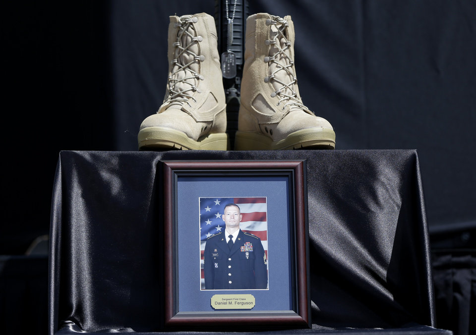 Photo - Part of a Soldiers Cross for Sgt. Danny Ferguson of Mulberry, Fla., is set near the stage before a memorial ceremony where President Barack Obama with speak, Wednesday, April 9, 2014, at Fort Hood, Texas, for those killed there in a shooting last week. President Barack Obama is reprising his role as chief comforter as he returns once again to a grief-stricken corner of America to mourn with the families of those killed last week at Fort Hood and offer solace to the nation. (AP Photo/Carolyn Kaster)