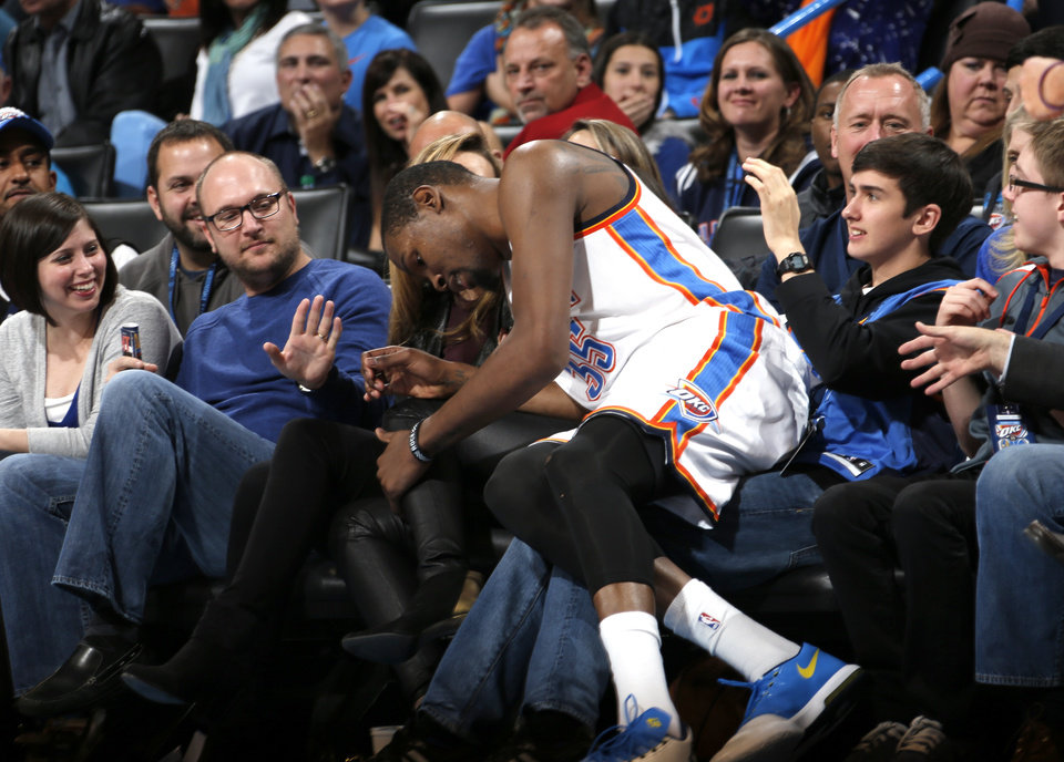 Photo - Oklahoma City's Kevin Durant (35) falls into the crowd during the NBA game between the Oklahoma City Thunder and the Golden State Warriors at the Chesapeake Energy Arena, Friday, Nov. 29, 2013. Photo by Sarah Phipps, The Oklahoman