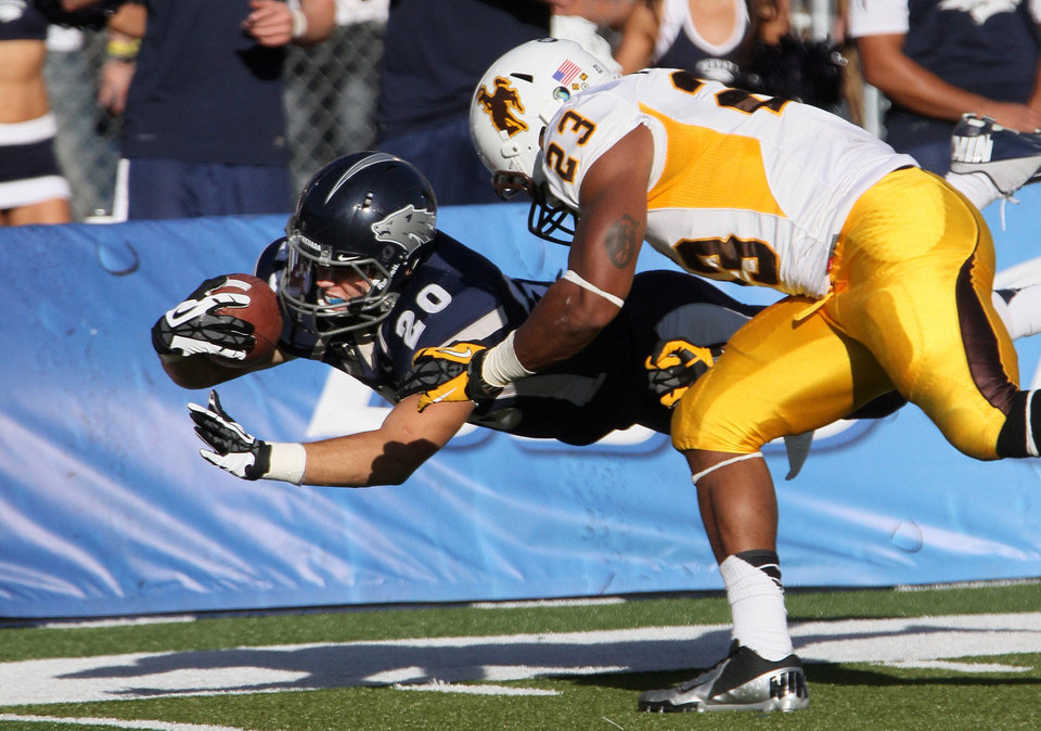 Photo -   Nevada's Kendall Brock (20) dives for the end zone as Wyoming defender Ghaali Muhammad (23) pushes Brock out-of-bounds short of the goal line during the first half of an NCAA college football game in Reno, Nev., on Saturday, Oct. 6, 2012. (AP Photo/Cathleen Allison)