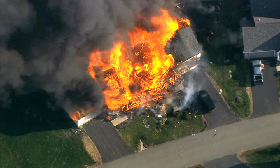 Photo - In this frame grab from television helicopter video, a home bursts into flames in Brentwood, N.H., Monday May 12, 2014.  Shots were fired just before the fire, which involved a police officer, according to the New Hampshire State Police. (AP Photo/WCVB-TV 5) TV OUT