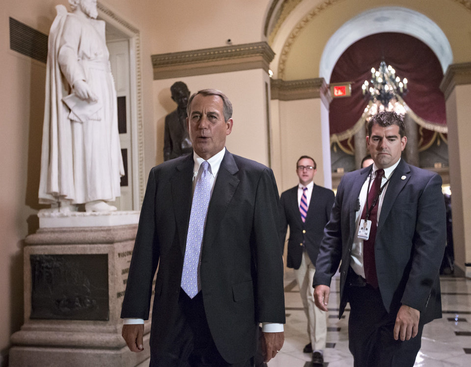 Photo - Speaker of the House John Boehner, R-Ohio, walks to the chamber as the House of Representatives works into the night to pass a bill to fund the government, at the Capitol in Washington, Saturday, Sept. 28, 2013. Locked in a deepening struggle with President Barack Obama, House Republicans on Saturday demanded a one-year delay in major parts of the nation's new health care law and permanent repeal of a tax on medical devices as the price for preventing a partial government shutdown threatened for early Tuesday. (AP Photo/J. Scott Applewhite)