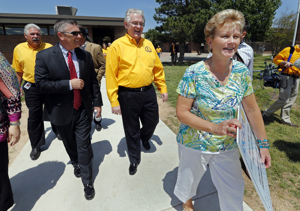 Photo - Sam Porter, disaster relief director, left, Moore Public Schools Superintendent Robert Romines, Baptist General Convention of Oklahoma executive director Anthony Jordan and Becky Jackson, principal at Central Elementary, walk to the proposed shelter site as they announce a donation for construction of a storm shelter Wednesday in Moore.  Photo by Steve Sisney, The Oklahoman  STEVE SISNEY