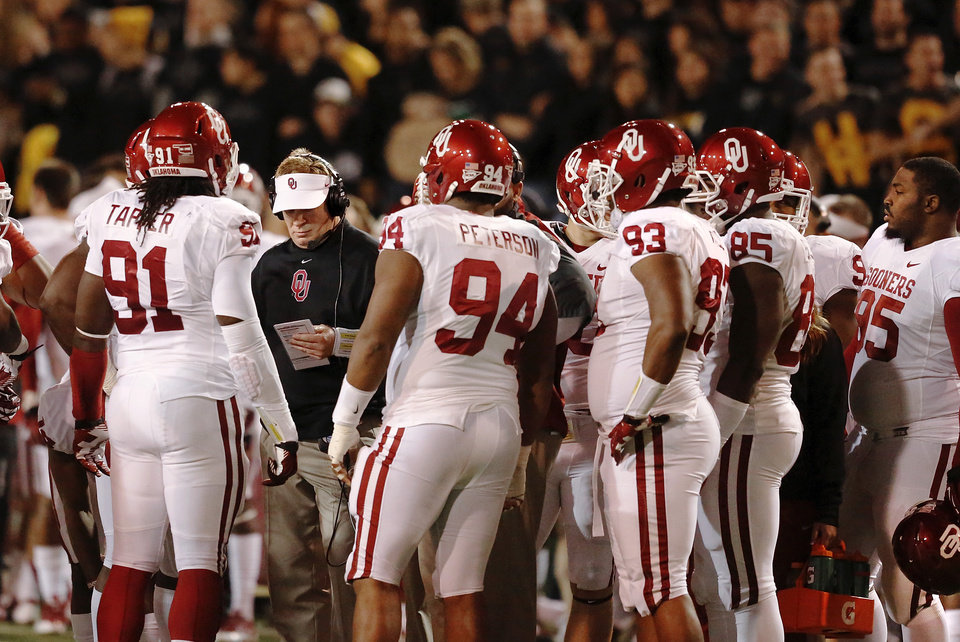 Defensive coordinator Mike Stoops is surrounded by players on the sideline during a timeout during first half action of the NCAA college football game between the University of Oklahoman (OU) Sooners and the Baylor Bears at Floyd Casey Stadium in Waco, Texas, Thursday, Nov. 7, 2013. Photo by Jim Beckel, The Oklahoman