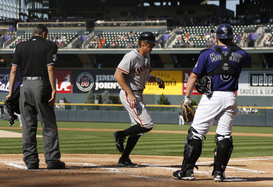 Photo - San Francisco Giants' Hunter Pence, center, crosses home plate after hitting a three-run home run as Colorado Rockies catcher Michael McKenry looks on in the first inning of a baseball game in Denver on Monday, Sept. 1, 2014. (AP Photo/David Zalubowski)