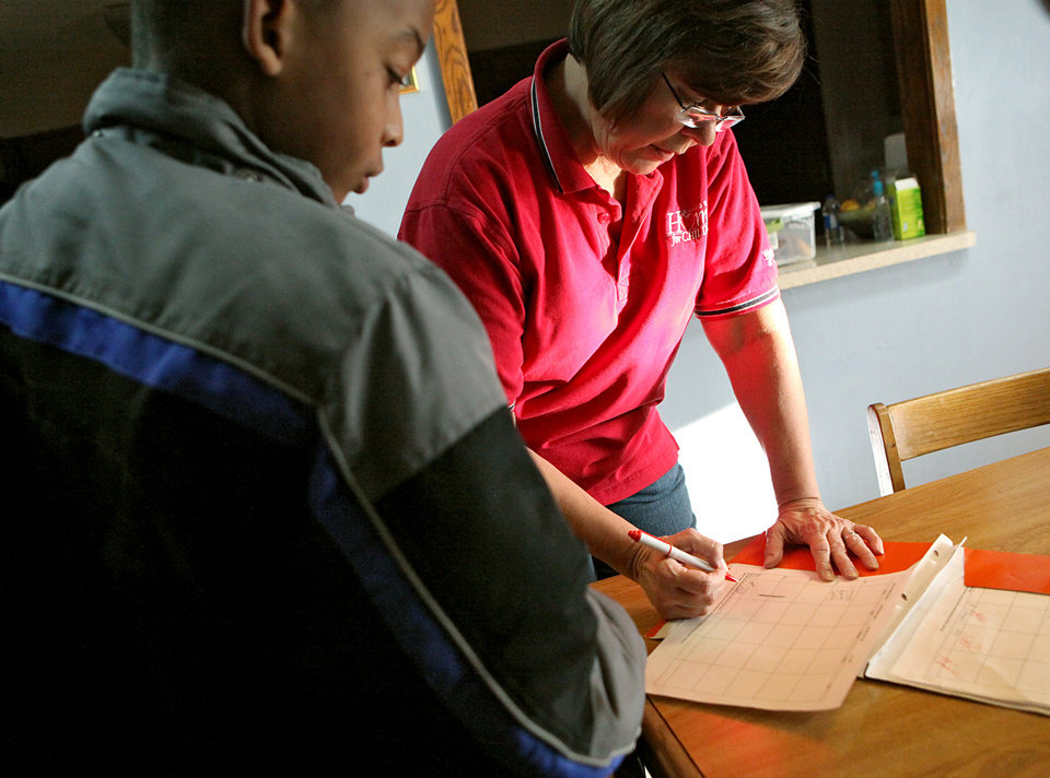 Photo - Harriet Hall, an associate house parent  at Boys Ranch Town in Edmond, goes over schoolwork with a resident on Monday, Nov. 30, 2009. By John Clanton, The Oklahoman ORG XMIT: KOD