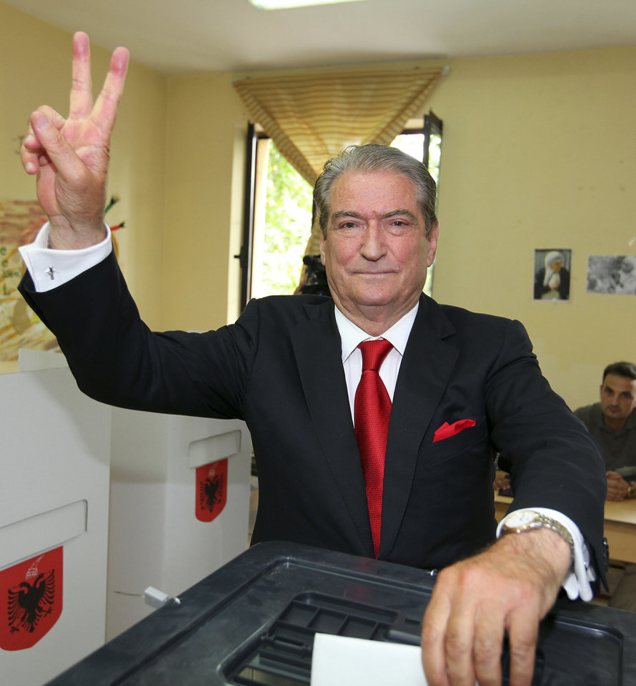 Photo - Prime Minister Sali Berisha of the Democratic Party gives a V sign and poses for photos before he casts his ballot during elections in Tirana, Albania, Sunday, June 23, 2013. Berisha and his close rival, Socialist leader Edi Rama, have hopes for eventual entry to the European Union, but the bloc has expressed concern over whether the country can manage to run fair and free elections. (AP Photo/Hektor Pustina)
