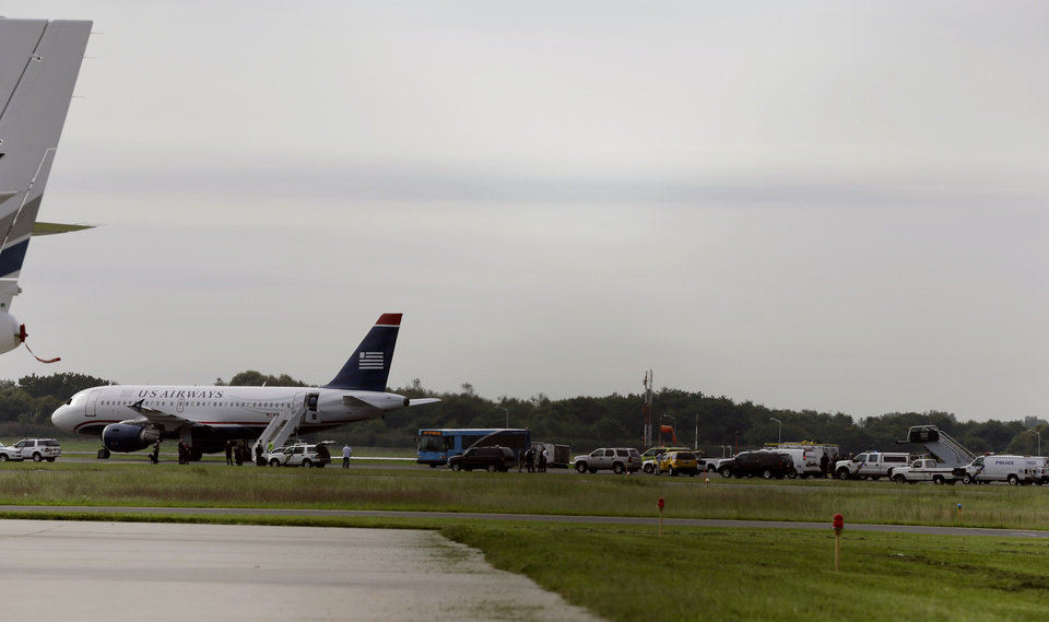 Photo -   Emergency personnel look over a US Airways plane at Philadelphia International Airport, after the plane returned to the airport, Thursday, Sept. 6, 2012, in Philadelphia. Airport spokeswoman Victoria Lupica says US Airways Flight 1267 returned to the airport Thursday morning as a