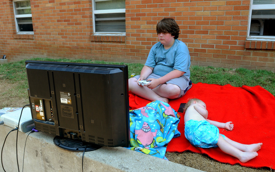 Photo -   Derek Longo, 11, plays a video game, powered by a running car engine hooked up to a power inverter, outside his home at Bruce Apartments in Ashland, Ky., on Monday, July 2, 2012, where the electricity was still out due to Friday's storm damage. Sleeping on ground next to him is Joseph DeLong, and under the blanket is Aaron Salyers. (AP Photo /The Daily Independent, Kevin Goldy)