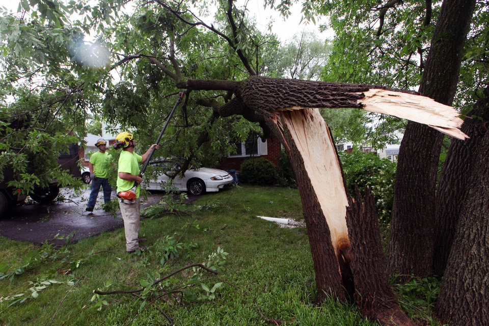 Ed Zunino and Kenny Price with Tree Huggerz clears debris from a home after a storm passed through, Thursday, June 13, 2013 in Hockessin, Del. A massive storm system that started in the Upper Midwest and plowed across the country was hitting the Mid-Atlantic Thursday, causing widespread power outages and flash flooding, but still largely failing to live up to its fierce billing. (AP Photo/The Wilmington News-Journal, Suchat Pederson)  NO SALES