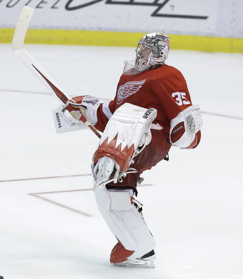 Photo - Detroit Red Wings goalie Jimmy Howard (35) celebrates after a 3-2 win after the shootout period of an NHL hockey game against the Los Angeles Kings in Detroit, Saturday, Jan. 18, 2014. (AP Photo/Carlos Osorio)