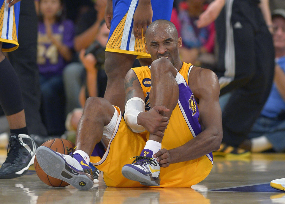 Photo - FILE - In this April 12, 2013 file photo, Los Angeles Lakers guard Kobe Bryant grimaces after being injured during the second half of their NBA basketball game against the Golden State Warriors, in Los Angeles. Bryant won't be back on the court for the Lakers this season. The Lakers said Bryant was examined by team physician Dr. Steve Lombardo, who determined that the left knee injury that has kept Bryant out of the lineup still hasn't healed.  (AP Photo/Mark J. Terrill, File)