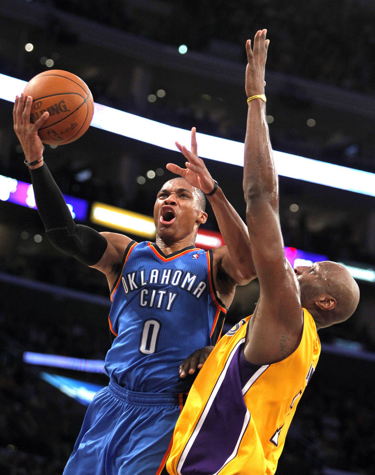 Photo - Oklahoma City Thunder guard Russell Westbrook (0) shoots as Los Angeles Lakers forward Lamar Odom (7) defends during the first half of an NBA basketball game Monday, Jan. 17, 2011, in Los Angeles. (AP Photo/Alex Gallardo) ORG XMIT: LAS201