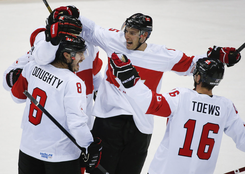 Photo - Team Canada celebrates a third period goal against Latvia during a men's quarterfinal ice hockey game at the 2014 Winter Olympics, Wednesday, Feb. 19, 2014, in Sochi, Russia. (AP Photo/Mark Humphrey)