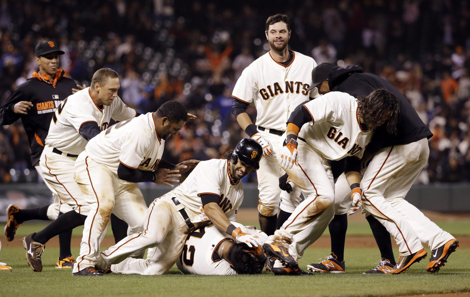 Photo - San Francisco Giants' Hector Sanchez, bottom center, is mobbed by teammates after driving in the game-winning run during the 12th inning of a baseball game against the Los Angeles Dodgers on Wednesday, April 16, 2014, in San Francisco. San Francisco won 3-2.  (AP Photo/Marcio Jose Sanchez)