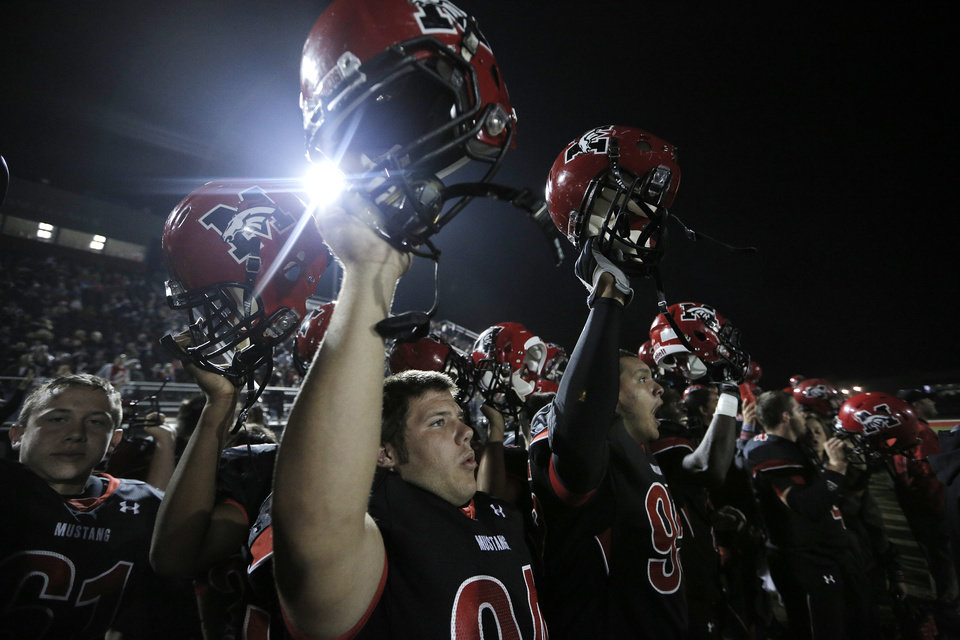 Photo - Mustang players hold up their helmets for a kickoff during a high school football game between Mustang and Stillwater in Mustang, Okla., Friday, Sept. 14, 2012.  Photo by Garett Fisbeck, The Oklahoman