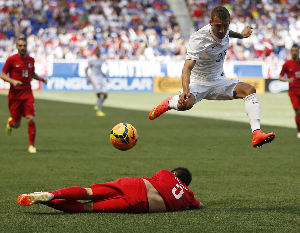 Photo - United States' Fabian Johnson, top, leaps over the slide tackle of Turkey's Ishak Dogan in the first half of an international soccer friendly, Sunday, June 1, 2014, in Harrison, N.J. (AP Photo/Julio Cortez)