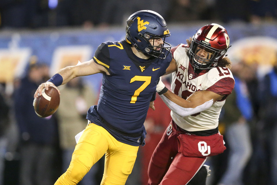 Photo - Oklahoma Sooners linebacker Curtis Bolton (18) attempts to sack West Virginia Mountaineers quarterback Will Grier (7) during the NCAA football game between the Oklahoma Sooners and the West Virginia Mountaineers at Mountaineer Field at Milan Puskar Stadium in Morgantown, W.Va on Friday, November 23, 2018. IAN MAULE/Tulsa World