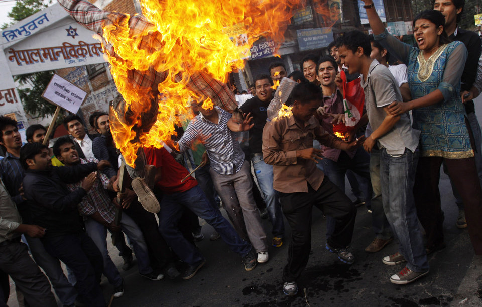 Photo -   Activists of Nepal's opposition parties burn an effigy of Prime Minister Baburam Bhattarai in Katmandu, Nepal, Wednesday, May 30, 2012. Nepal sank into political turmoil after lawmakers failed to agree on a new constitution, leaving the country with no legal government. Nepal's opposition parties said they will team up to topple the government, as they accused the prime minister Wednesday of having no moral or legal grounds to stay in power ahead of new elections. (AP Photo/Binod Joshi)