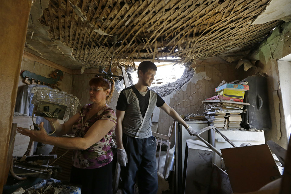 Photo - Local residents Andrei Avdyukhin, right, and his mother Svetlana inspect the damage in their destroyed house after shelling in Donetsk, eastern Ukraine, Thursday, Aug. 14, 2014. A rebel-held city in eastern Ukraine came under intensified shelling Wednesday as the U.N. revealed that the death toll from the fighting between government troops and separatists has nearly doubled in the last two weeks. (AP Photo/Sergei Grits)