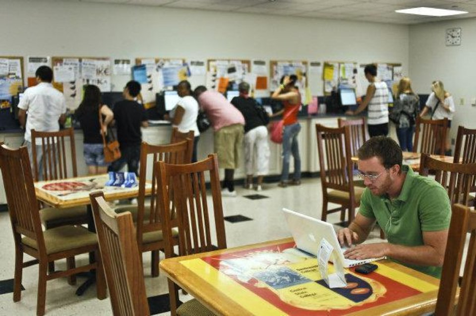 Photo - Stuart Arnett works on the enrollment process at the University of Central Oklahoma on Wednesday while other students check bulletin boards for information. PHOTO BY CHRIS LANDSBERGER, THE OKLAHOMAN  CHRIS LANDSBERGER - CHRIS LANDSBERGER