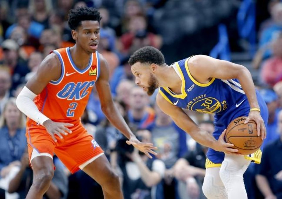 Photo -  Golden State's Stephen Curry, right, looks to get around Oklahoma City's Shai Gilgeous-Alexander during Sunday's game at Chesapeake Energy Arena. The Thunder won the game, 120-92. [Sarah Phipps/The Oklahoman]