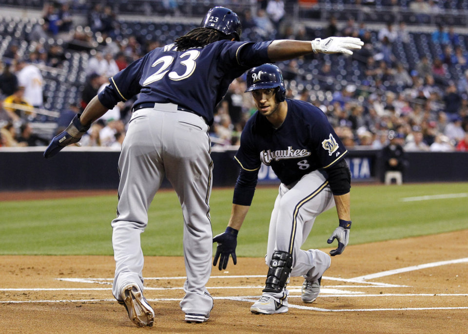 Milwaukee Brewers' Ryan Braun, right, is congratulated by Rickie Weeks (23) after hitting a two-run home run against the San Diego Padres in the first inning of a baseball game, Monday, April 22, 2013, in San Diego. (AP Photo/Alex Gallardo)